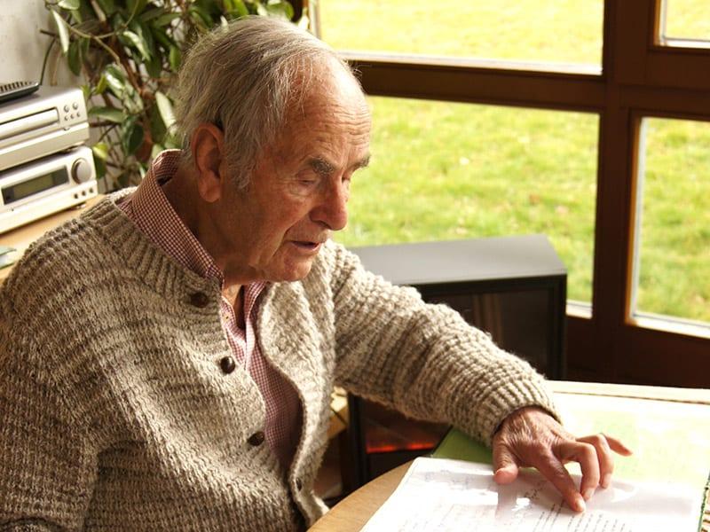 Josef Ertl sitzt an einem Tisch und schaut sich Liedtexte durch.