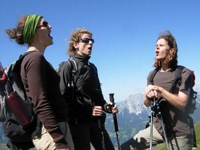 Drei Personen jodeln in den Bergen