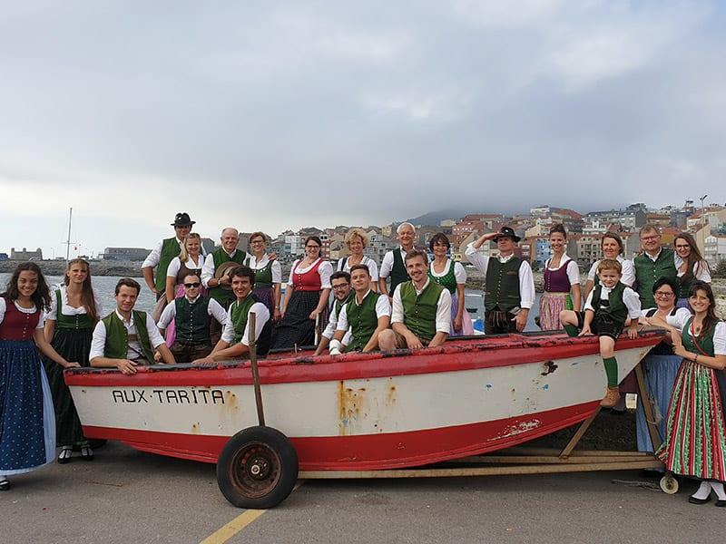 Die Volkstanzsgruppe posiert bei einem Fischerboot in Spanien.