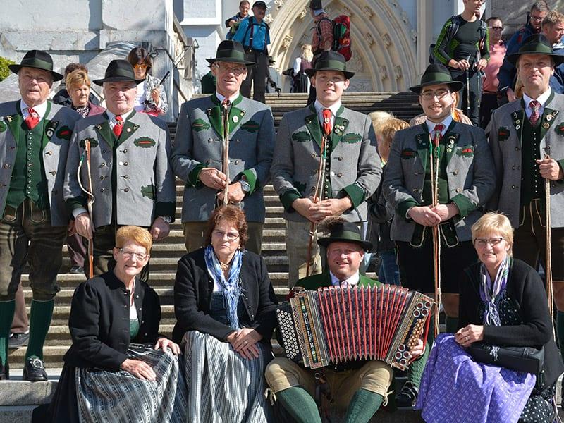 """Eine Gruppe """"Goaßlschnalzer"""" mit einem Harmonikaspieler."""