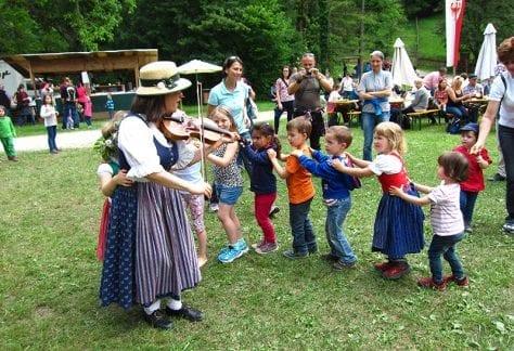 Kinder folgen tanzend einer Geigenspielerin